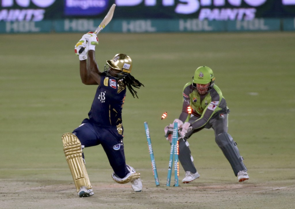 Quetta Gladiators' Chris Gayle, left, is bowled out by Lahore Qalandars' Rashid Khan while teammate Ben Dunk watches during a Pakistan Super League T2...