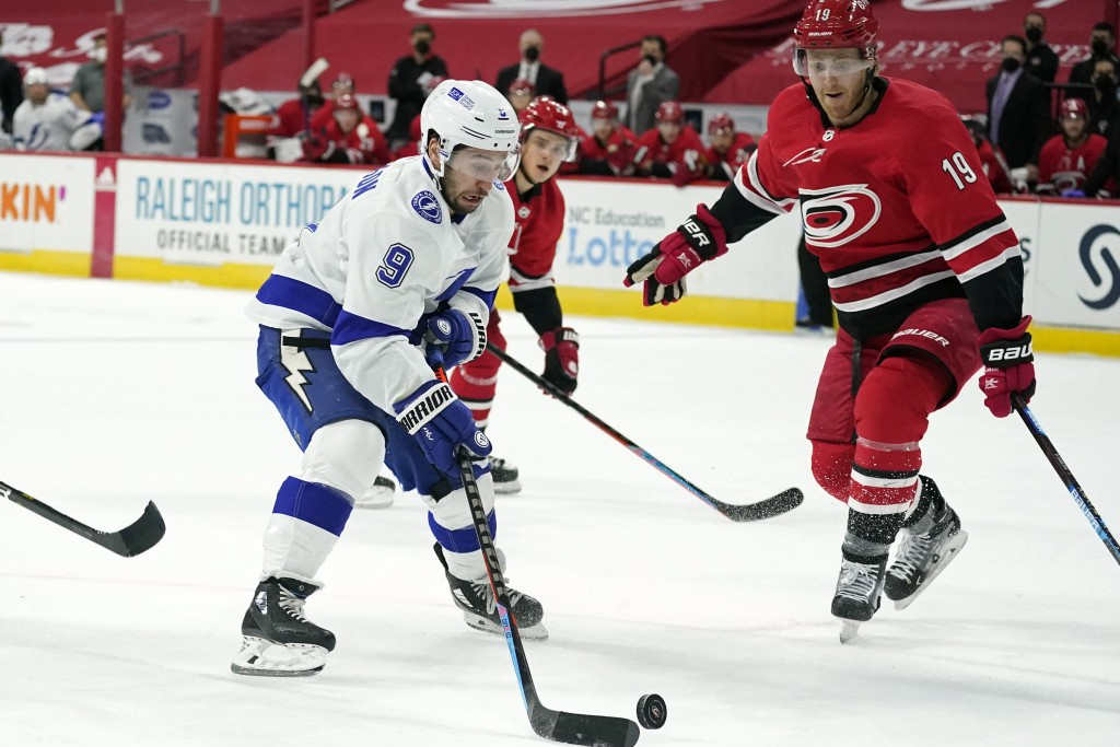 Tampa Bay Lightning center Tyler Johnson (9) looks to shoot as Carolina Hurricanes defenseman Dougie Hamilton (19) defends during the first period of ...