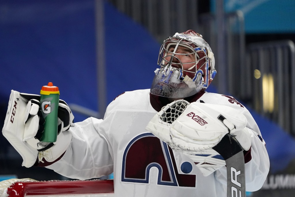 Colorado Avalanche goaltender Philipp Grubauer grabs his water bottle after giving up a goal to Vegas Golden Knights right wing Alex Tuch in the secon...