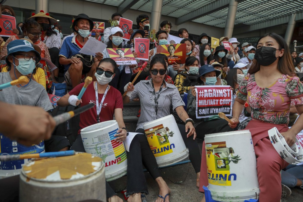 Anti-coup protesters beat plastic containes during a demonstration in Yangon, Myanmar, Tuesday, Feb. 23, 2021. Protesters gathered in Myanmar's bigges...