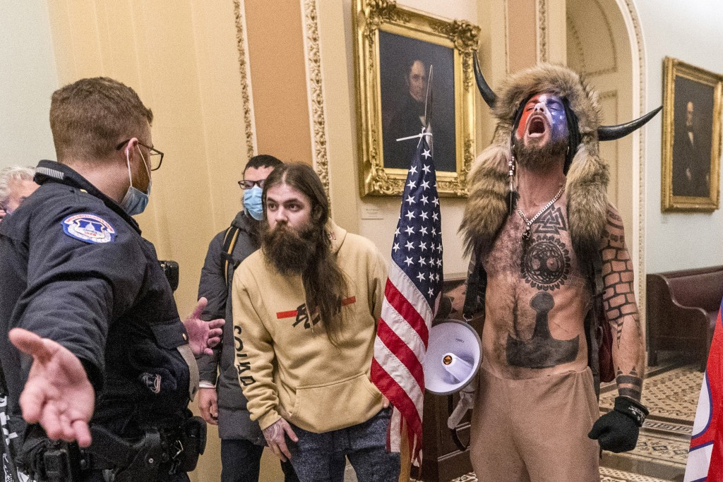 FILE - In this Wednesday, Jan. 6, 2021 file photo, supporters of President Donald Trump, including Jacob Chansley, right with fur hat, are confronted ...