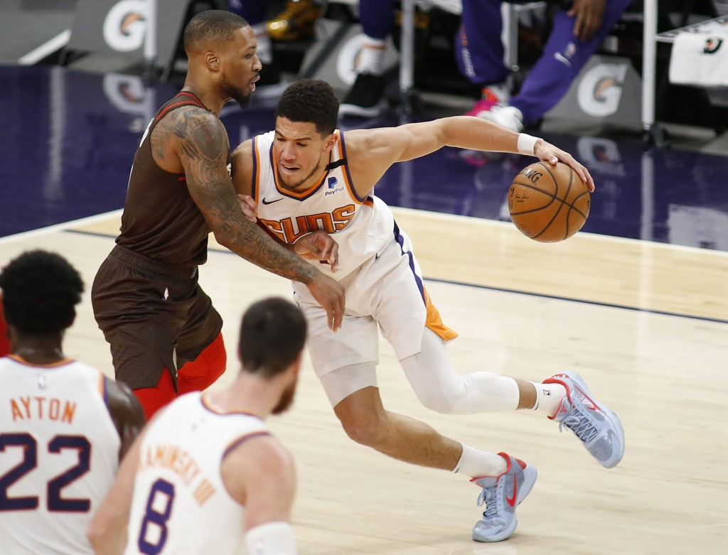 Phoenix Suns' Devin Booker muscles his way towards the basket against Portland Trail Blazers' Damien Lillard during the first half of an NBA basketbal...