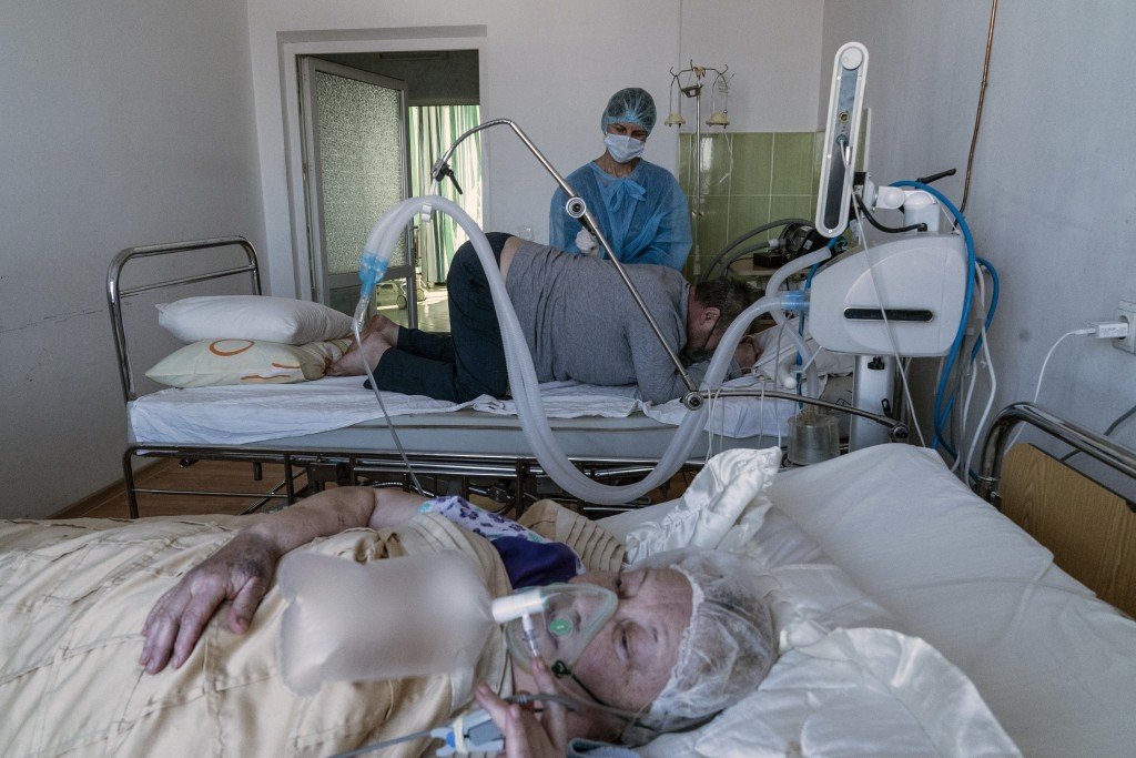 An elderly woman suffering from COVID-19 breathes with the help of an oxygen mask, foreground, as a nurse treats a patient in central district hospita...