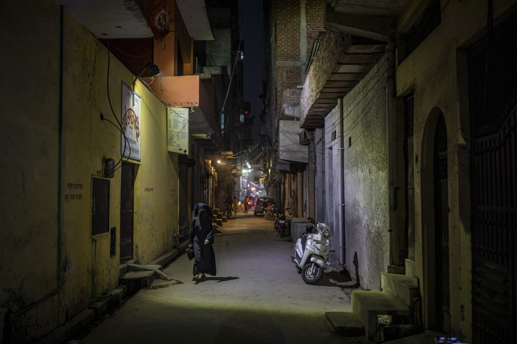 A burqa clad Muslim woman walks in an alleyway in North Ghonda neighborhood, one of the worst riot affected area during the February 2020 communal rio...