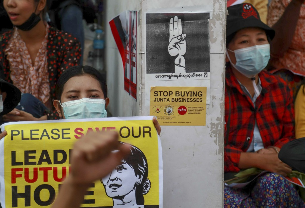 Anti-coup protesters sitting next to signs to boycott Myanmar military-linked business, display a picture of deposed Myanmar leader Aung San Suu Kyi d...