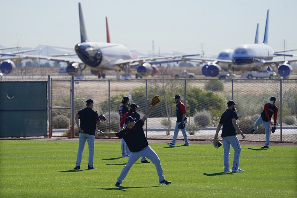 With mothballed and retired passenger planes in the background at Phoenix Goodyear Airport, pitchers for the Cleveland Indians warm up during a spring...