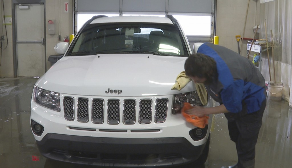 In this image made from video, a worker washes a Jeep inside the service department of a LaFontaine auto dealership in Fenton Township, Mich., Thursda...