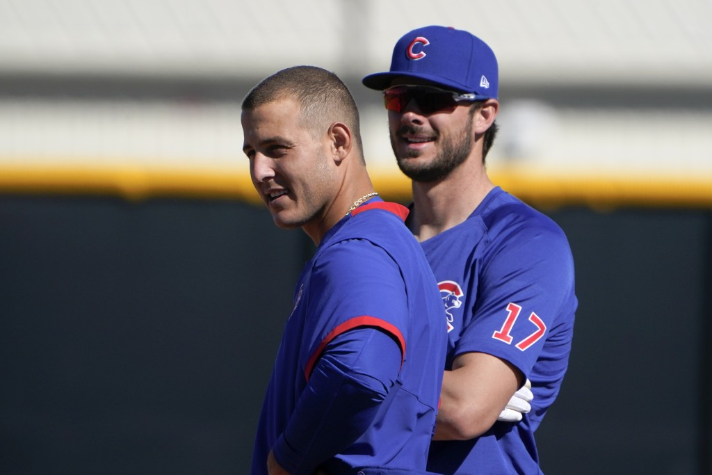 Chicago Cubs' Anthony Rizzo, left, and Kris Bryant stand on the field during a spring training baseball workout in Mesa, Ariz., Monday, Feb. 22, 2021....