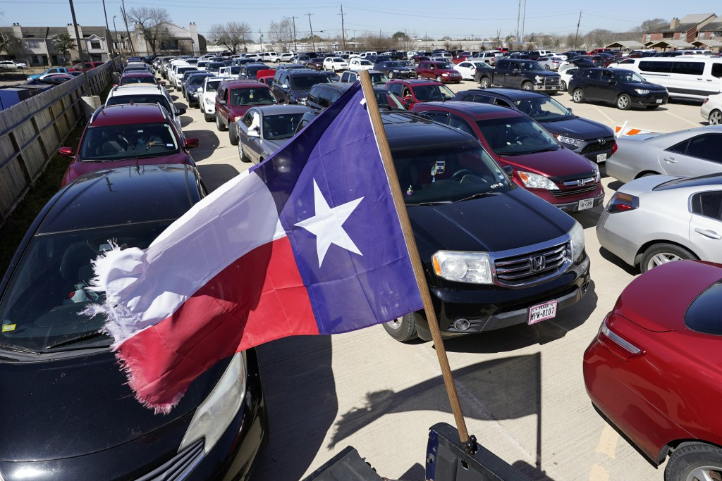 Hundreds of a vehicles are staged in a parking lot as people wait in line at a food and water distribution site Monday, Feb. 22, 2021, in Houston. The...