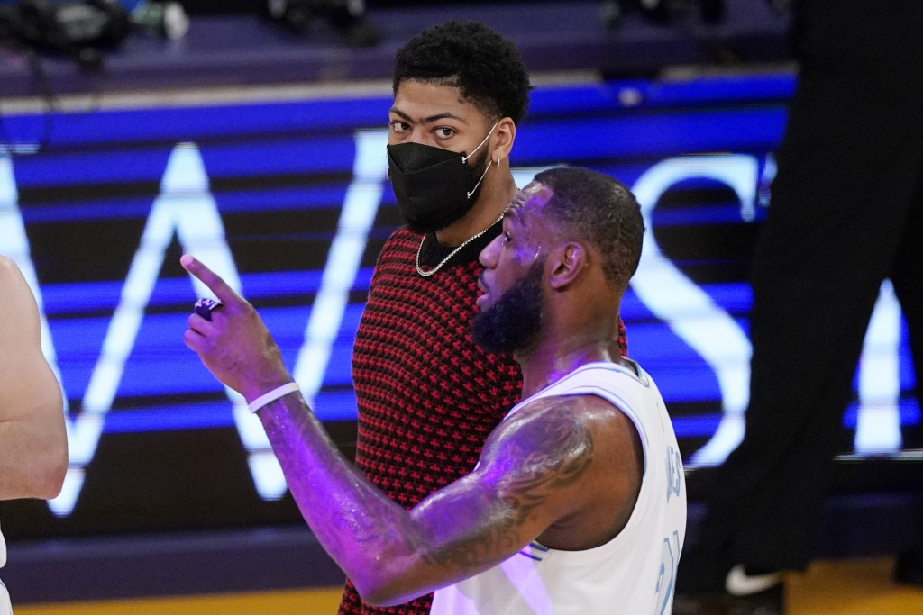 Los Angeles Lakers forward LeBron James, right, talks with Anthony Davis during the first half of an NBA basketball game against the Washington Wizard...