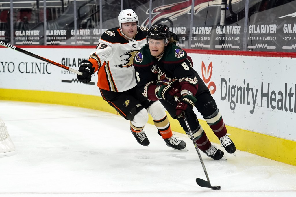 Arizona Coyotes defenseman Jakob Chychrun (6) shields the puck from Anaheim Ducks left wing, Max Jones, in the first period during an NHL hockey game,...