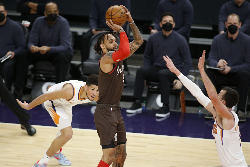 Portland Trail Blazers' Gary Trent Jr. puts up a shot against the Phoenix Suns' Frank Kaminsky III as Devin Booker looks on during the first half of a...
