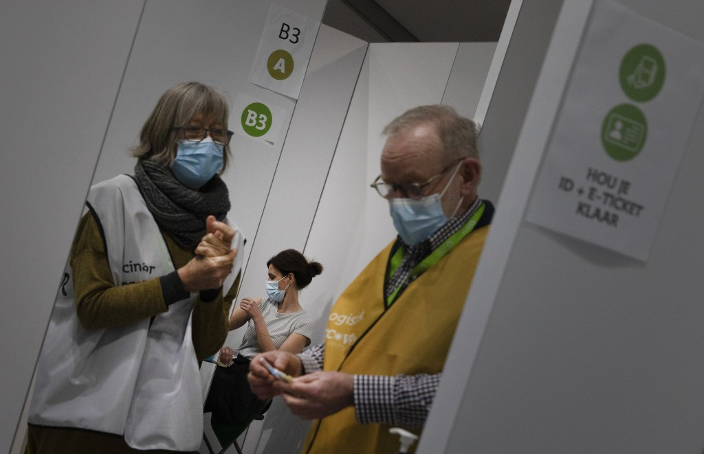 FILE - In this Friday, Feb. 19, 2021 file photo, A logistics officer, right, and a vaccinator, left, prepare to administer an injection of the AstraZe...