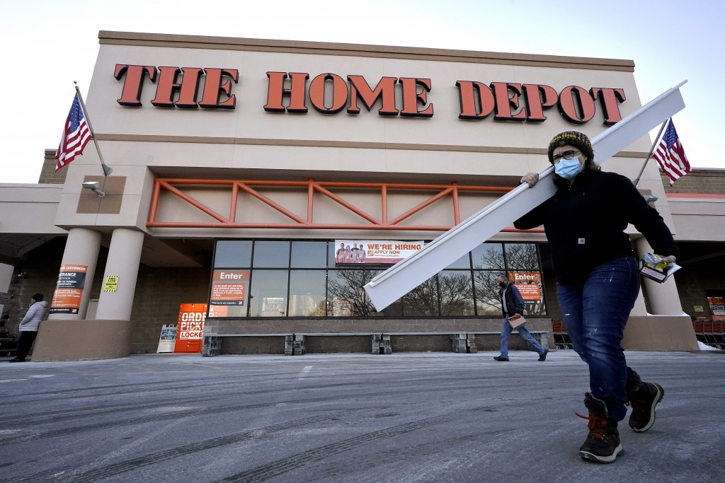Passers-by walk near an entrance to a Home Depot home improvement store Sunday, Feb. 21, 2021, in Boston. The Home Depot's fiscal fourth-quarter sales...