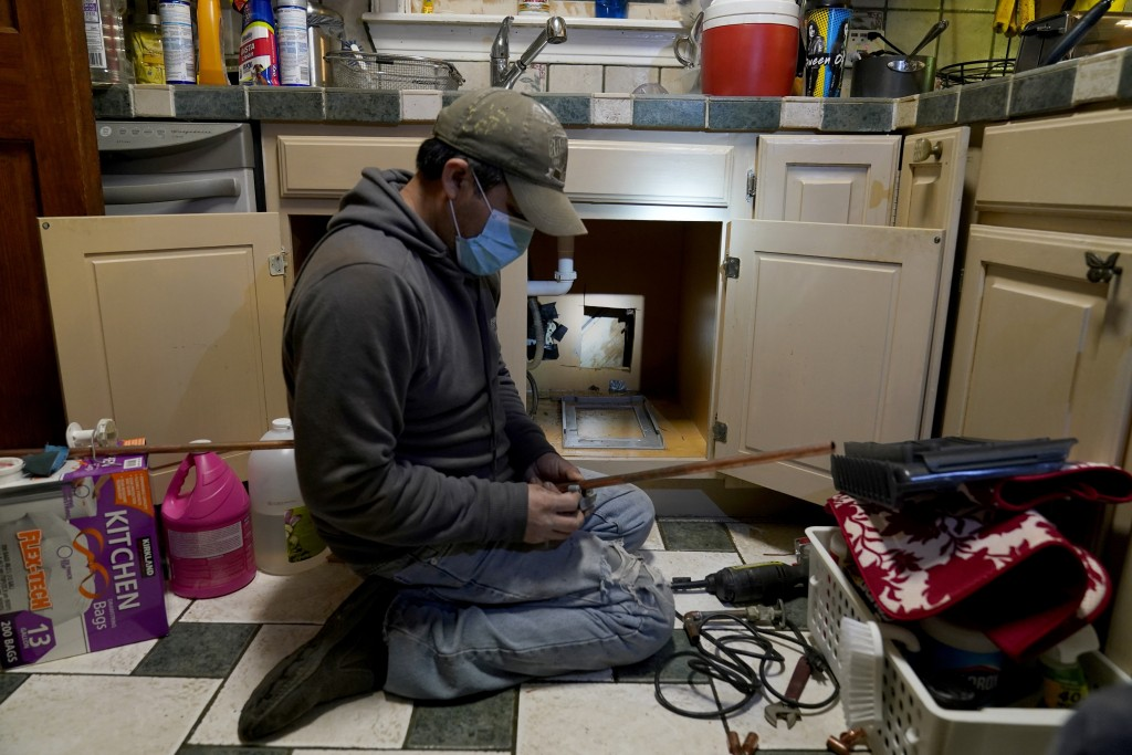 CORRECTS SPELLING OF LAST NAME TO VALERIO, NOT VALERIA - Handyman Roberto Valerio works on repairing a broken pipe beneath the sink in the home of Nor...