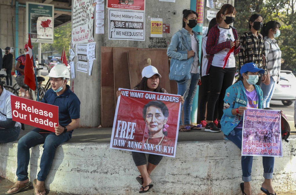 Anti-coup protesters display pictures of deposed Myanmar leader Aung San Suu Kyi as they gather to protest in Yangon, Myanmar Tuesday, Feb. 23, 2021. ...