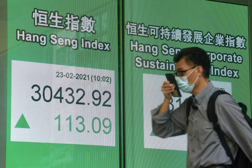 A man wearing a face mask walks past a bank's electronic board showing the Hong Kong share index in Hong Kong, Tuesday, Feb. 23, 2021. Asian shares we...