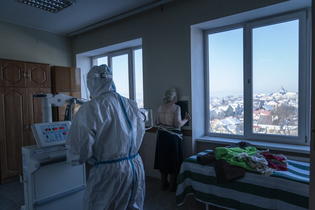 A medic wearing a special suit to protect against coronavirus, back to a camera prepares a patient with coronavirus for a lung X-ray at a hospital in ...