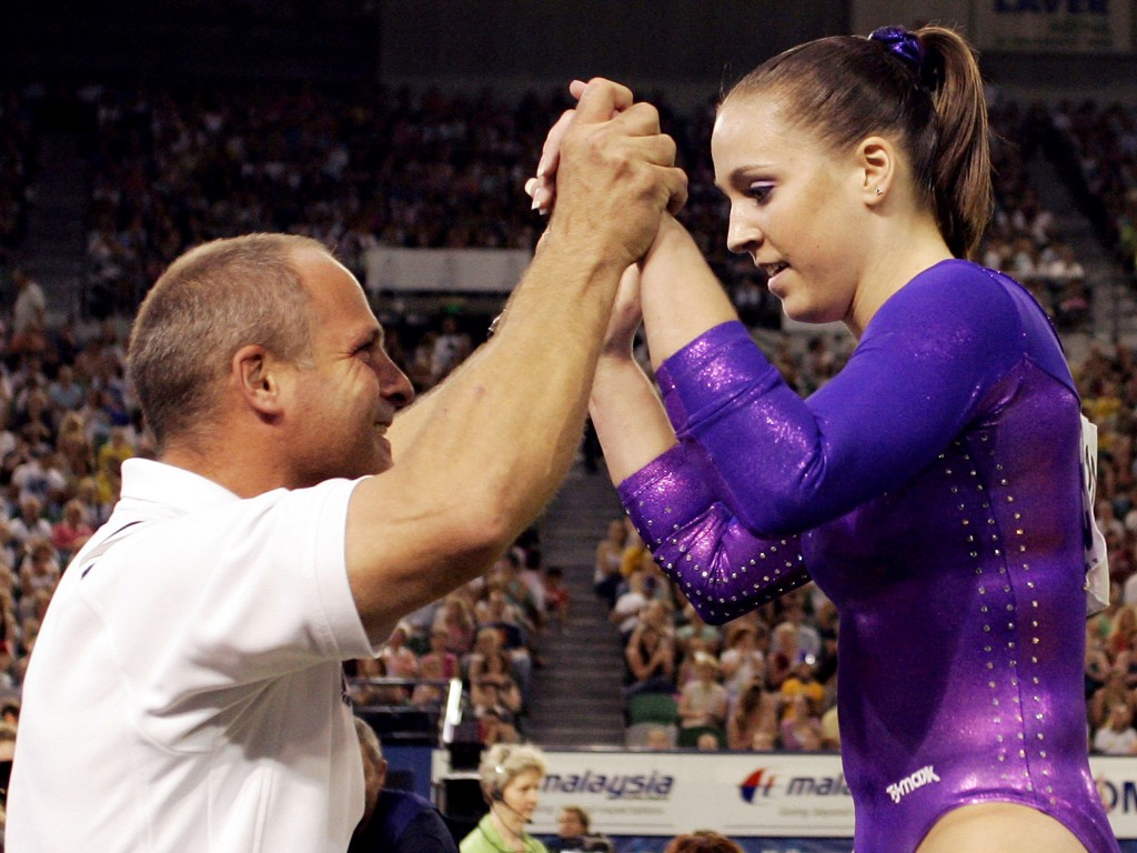 FILE - Chellsie Memmel is congratulated by her coach and father, Andrew Memmel, after completing her routine on the Floor Exercise in the final of the...