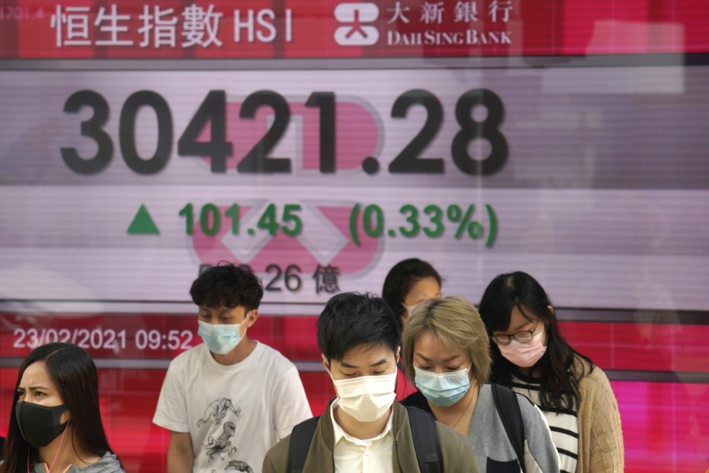 People wearing face masks walk past a bank's electronic board showing the Hong Kong share index in Hong Kong, Tuesday, Feb. 23, 2021. Asian shares wer...