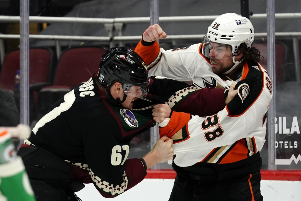 Arizona Coyotes left wing Lawson Crouse (67) and Anaheim Ducks center Derek Grant (38) fight in the first period during an NHL hockey game, Monday, Fe...