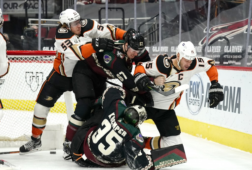 Anaheim Ducks left wing Max Comtois (53) and center Ryan Getzlaf (15) fight with Arizona Coyotes left wing Lawson Crouse (67) and goaltender Darcy Kue...