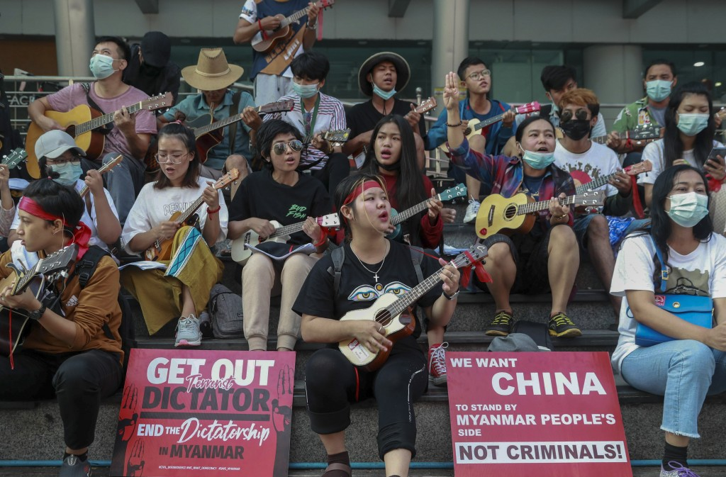 An anti-coup protester flashes the three-fingered salute as others play instruments and sing in Yangon, Myanmar, Tuesday, Feb. 23, 2021. Protesters ga...