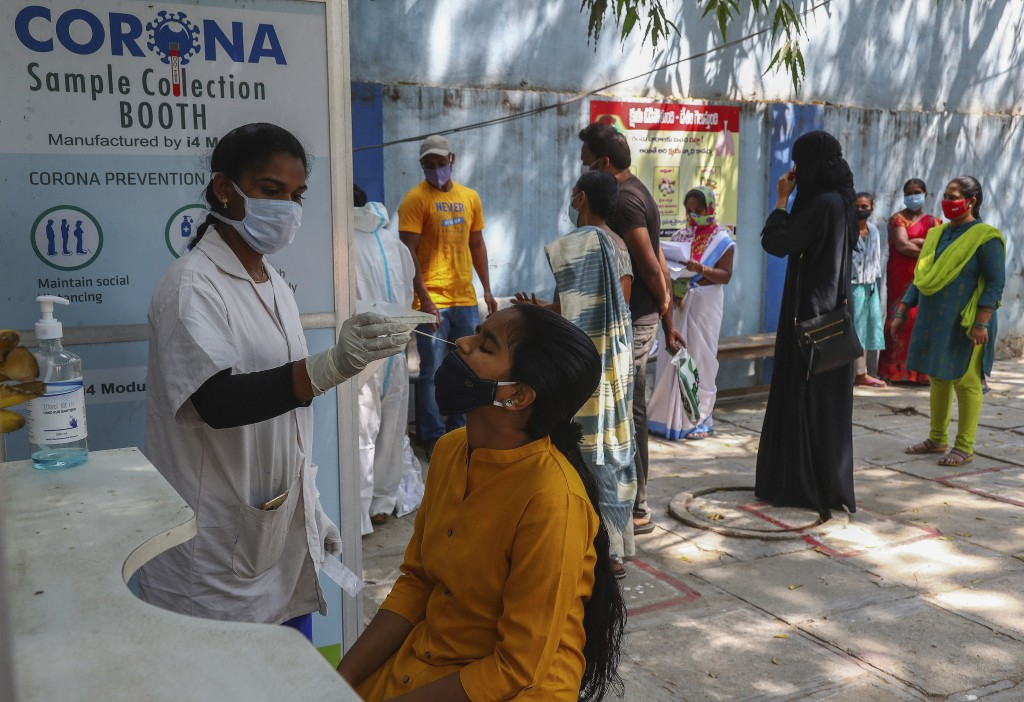 A health worker takes a nasal swab sample at a COVID-19 testing center in Hyderabad, India, Tuesday, Feb. 23, 2021. Cases of COVID-19 are increasing i...