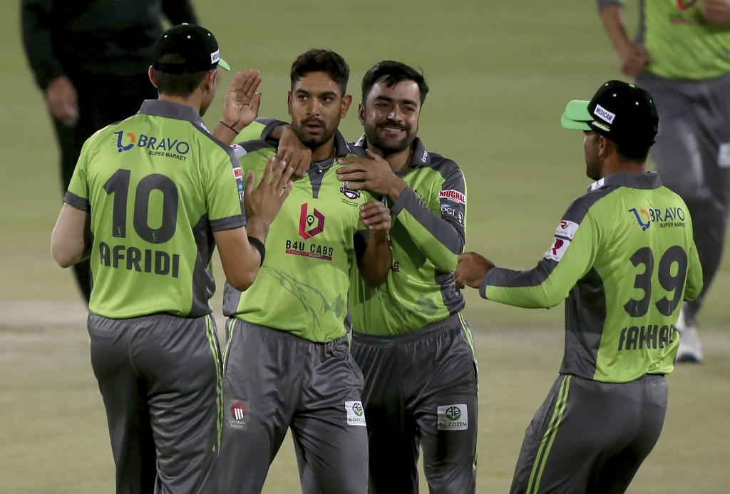 Lahore Qalandars' Haris Rauf, second left, celebrates with teammates after after taking the wicket of Quetta Gladiators' Tom Banton during a Pakistan ...