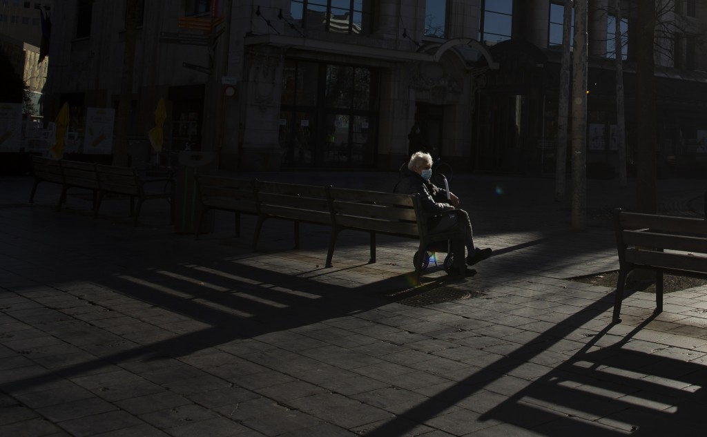 FILE - In this Tuesday, Nov. 3, 2020 file photo, a man sits alone on a park bench in the historical center of Antwerp, Belgium. The government on Mond...