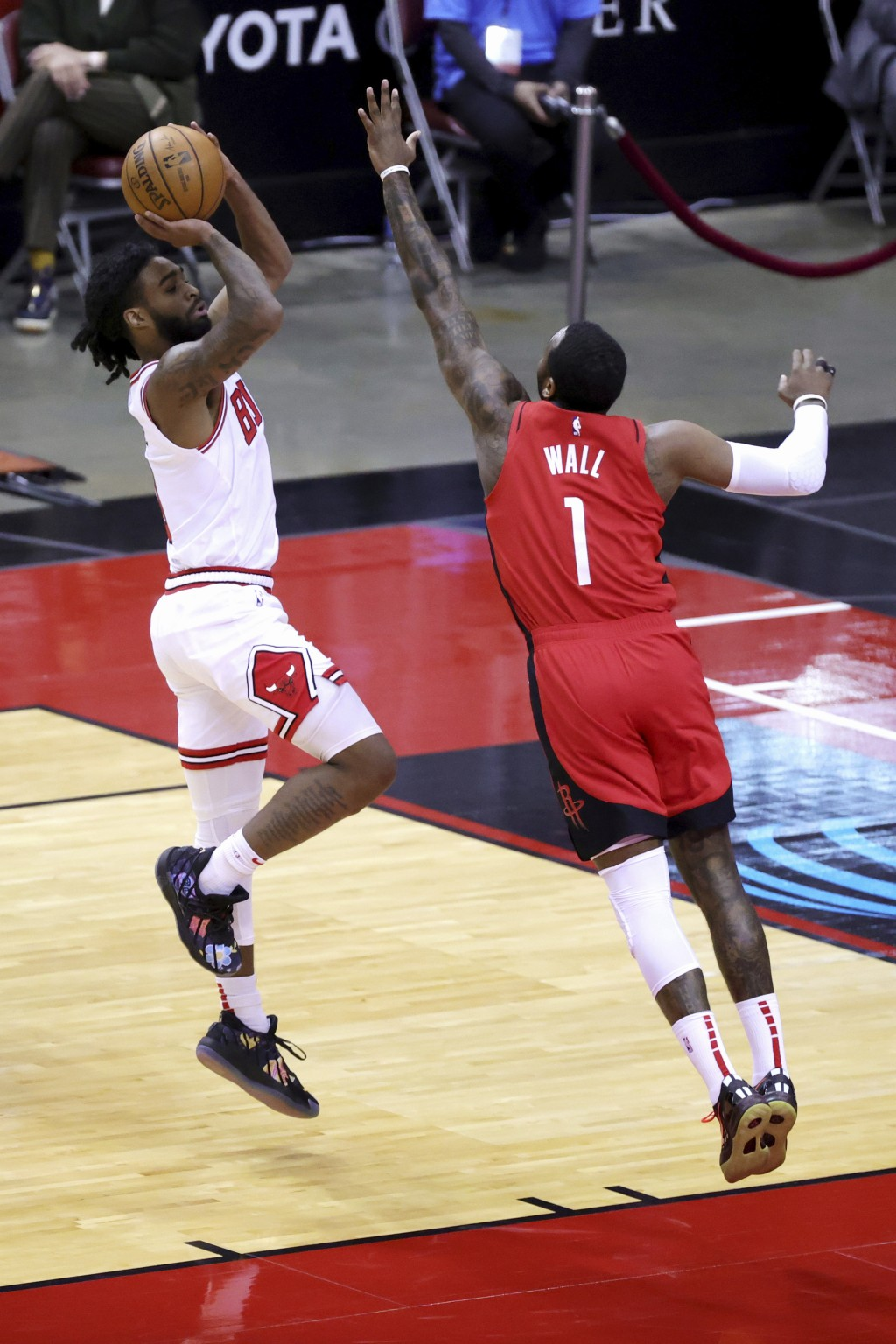 chicago Bulls' Coby White, left, puts up a jump shot ahead of Houston Rockets' John Wall (1) during the first quarter of an NBA basketball game Monday...