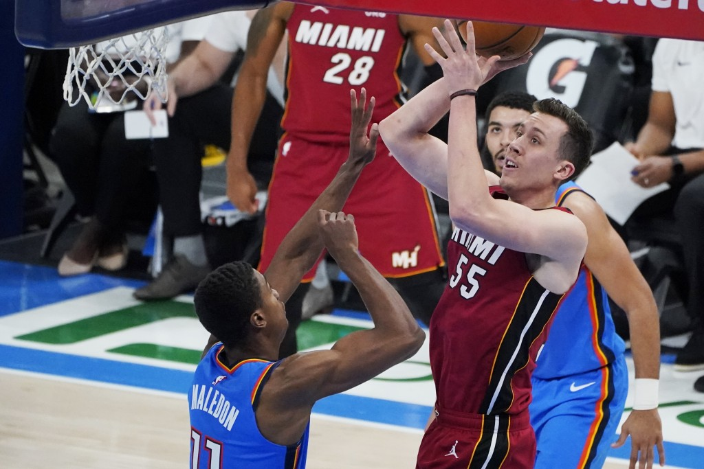 Miami Heat guard Duncan Robinson (55) shoots between Oklahoma City Thunder guard Theo Maledon, left, and guard Kenrich Williams, right, in the second ...