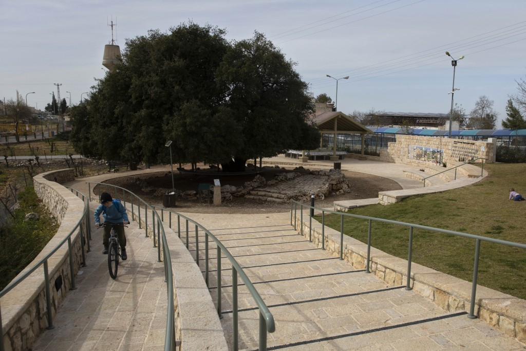 An Israeli Jewish settler youth rides a bicycle on a small promenade built by the Jewish National Fund, also known by its Hebrew acronym KKL, near the...