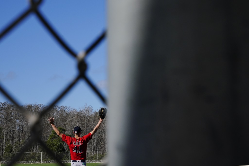 Boston Red Sox pitcher Chris Sale stretches before he runs onto the field to workout during spring training baseball practice on Monday, Feb. 22, 2021...