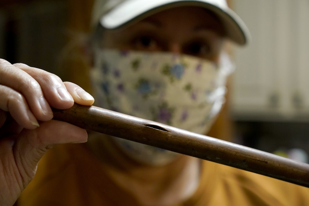 CORRECTS SPELLING OF LAST NAME TO VALERIO, NOT VALERIA - Homeowner Nora Espinoza holds a piece of the broken pipe removed by handyman Roberto Valerio ...