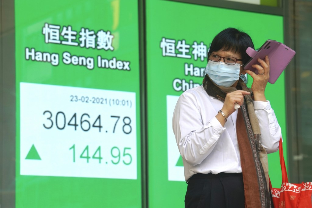 A woman wearing a face mask uses her mobile phone at a bank's electronic board showing the Hong Kong share index in Hong Kong, Tuesday, Feb. 23, 2021....
