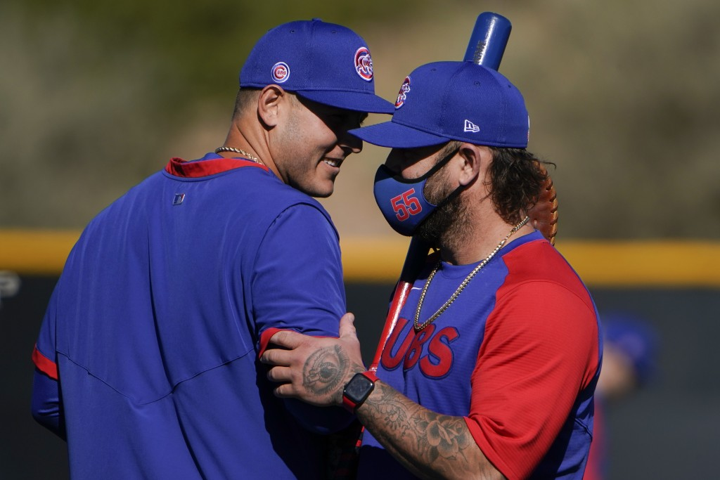 Chicago Cubs' Anthony Rizzo, left, shares a light moment with coach Mike Napoli during the team's spring training baseball workout in Mesa, Ariz., Mon...