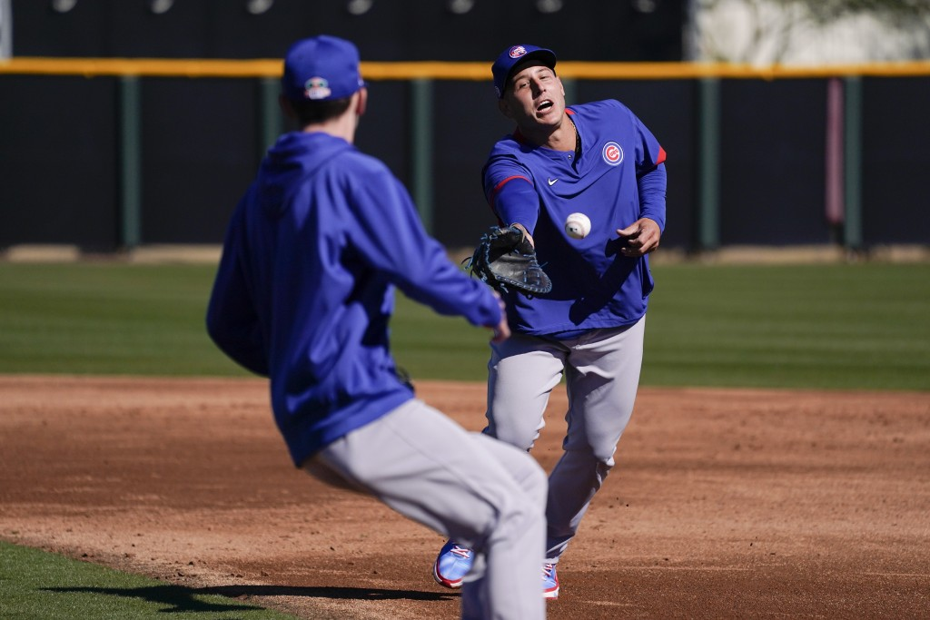 Chicago Cubs' Anthony Rizzo, right, tosses the ball to a pitcher during the team's spring training baseball workout in Mesa, Ariz., Monday, Feb. 22, 2...