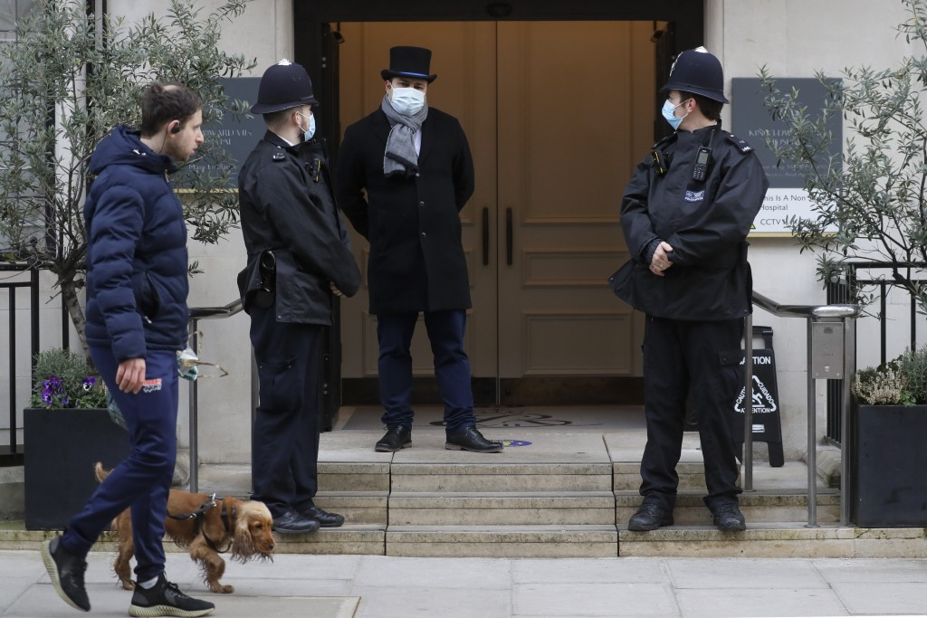 A man walks by with a dog as police officers stand outside King Edward VII's hospital in London, Tuesday, Feb. 23, 2021. Britain's Prince Philip was a...