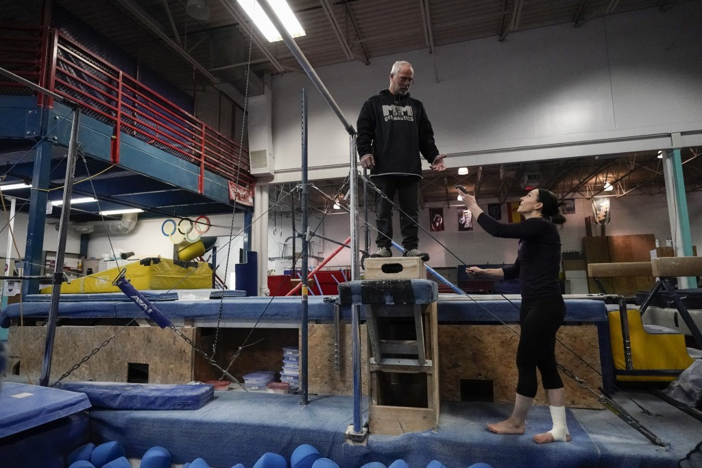 Former gymnastics world champion and Olympic silver medalist Chellsie Memmel works out with her father and coach Andy Memmel Thursday, Feb. 18, 2021, ...