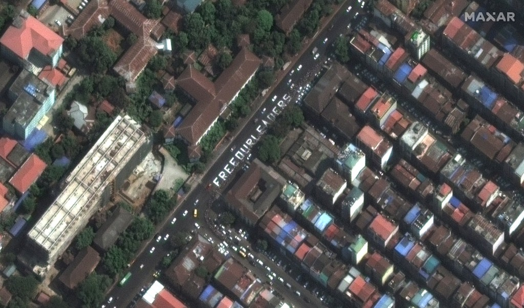 """This satellite image provided by Maxar Technologies shows a painting of letters that reads, """"FREE OUR LEADERS,"""" on a street in Yangon, Myanmar, Monday..."""