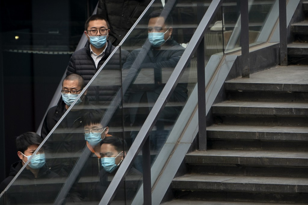 People wearing face masks to protect against the spread of the coronavirus ride an escalator at an office and shopping complex in Beijing, Tuesday, Fe...