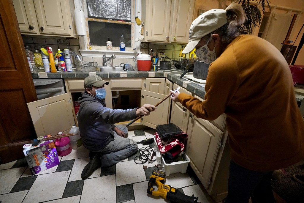 CORRECTS SPELLING OF LAST NAME TO VALERIO, NOT VALERIA - Handyman Roberto Valerio, left, hands homeowner Nora Espinoza the broken pipe after removing ...