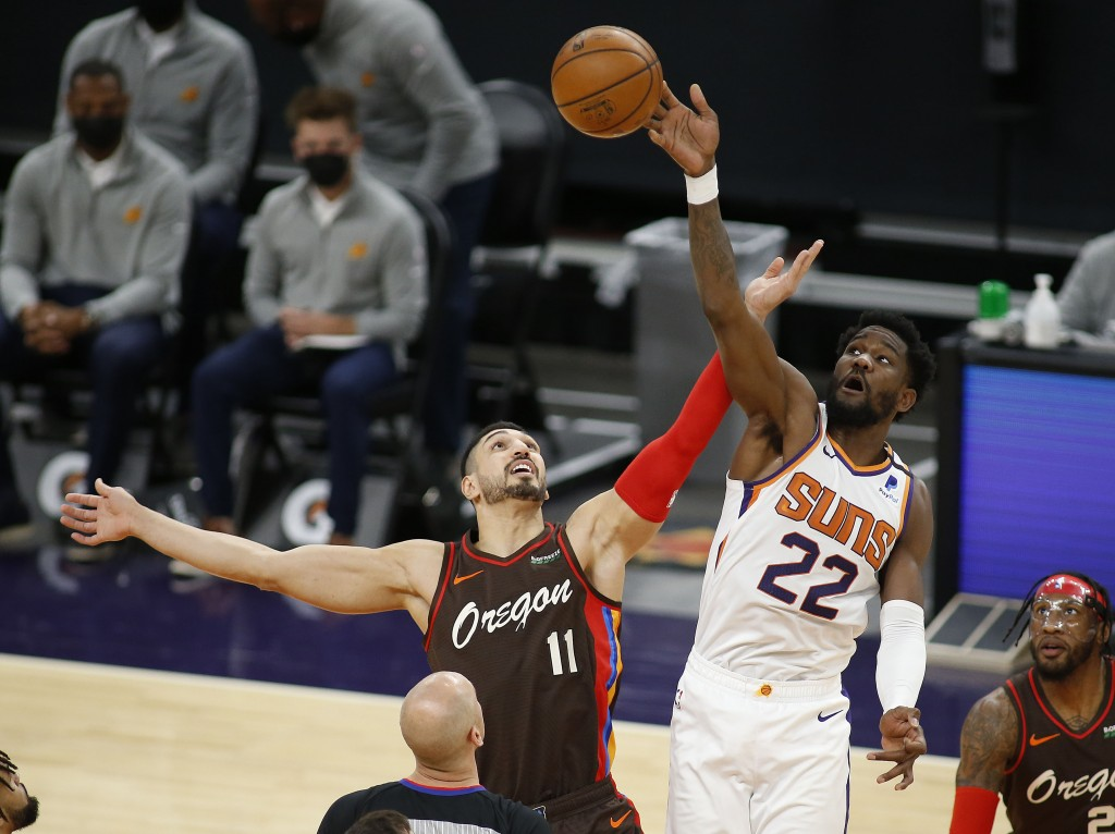 Phoenix Suns' Deandre Ayton wins the tip-off against the Portland Trail Blazers' Enes Kanter during the first half of an NBA basketball game Monday, F...