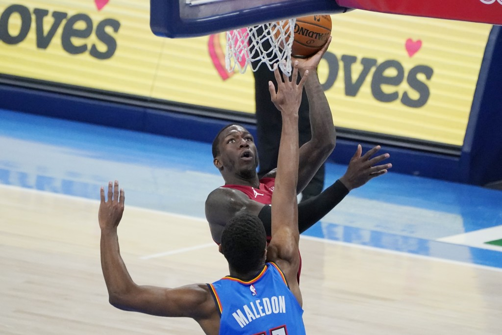 Miami Heat guard Kendrick Nunn, rear, shoots in front of Oklahoma City Thunder guard Theo Maledon, front in the second half of an NBA basketball game ...