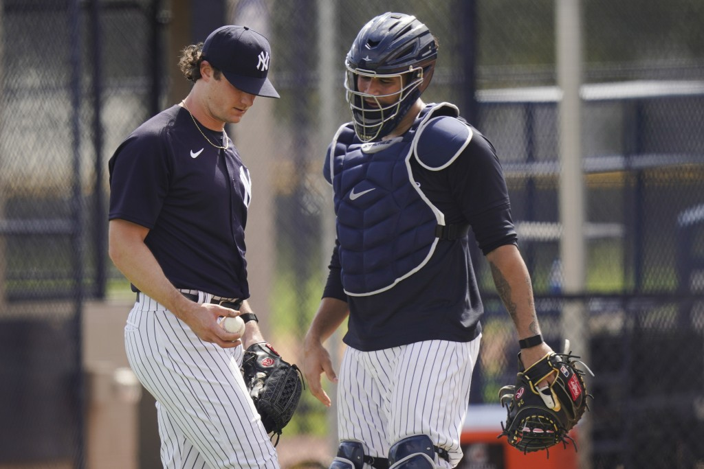New York Yankees' Gerrit Cole, left, talks to catcher Gary Sanchez after a spring training baseball workout Monday, Feb. 22, 2021, in Tampa, Fla. (AP ...
