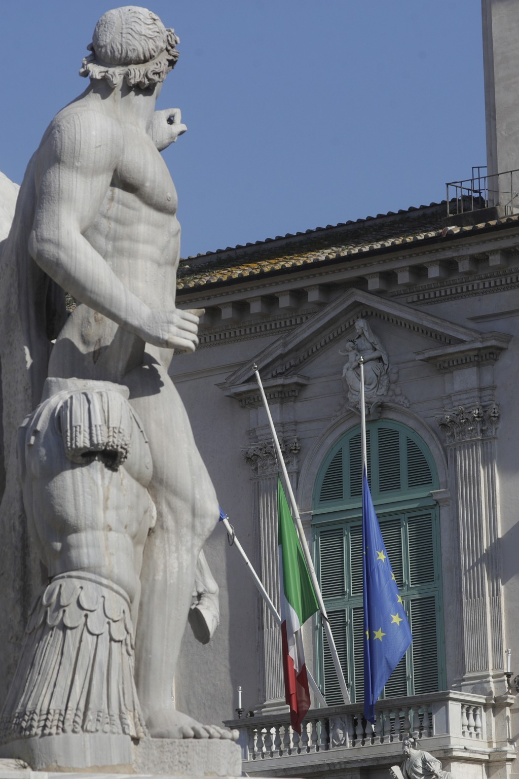 The flags of Italy and the EU, right, fly at half mast outside the Quirinale, Presidential palace, in Rome, Tuesday, Feb. 23, 2021. The Italian ambass...