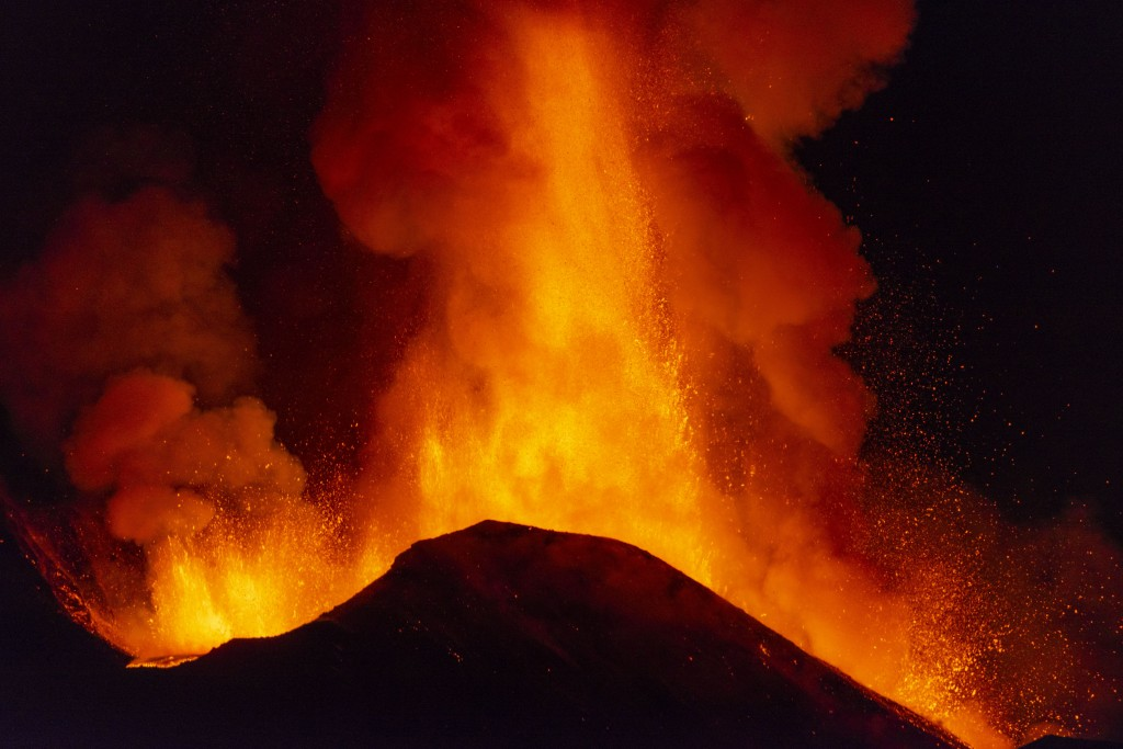 Lava spews during an eruption of Mt. Etna volcano, near Catania in Sicily, southern Italy, late Monday, Feb. 22, 2021. The explosion started before mi...