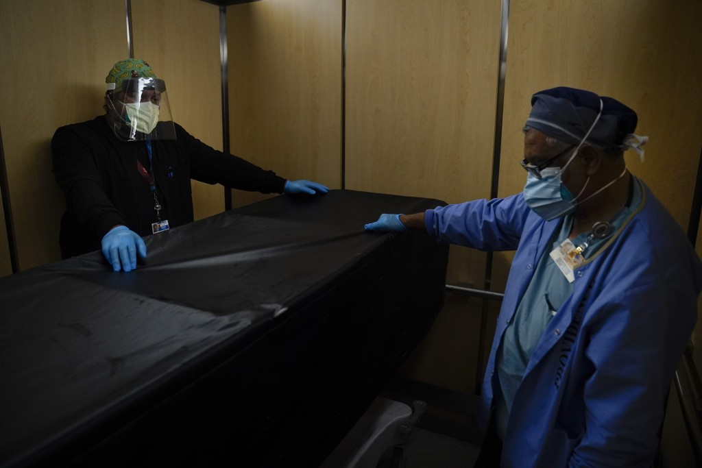 FILE - In this Jan. 9, 2021, file photo, transporters Miguel Lopez, right, Noe Meza move a body of a COVID-19 patient to a morgue at Providence Holy C...