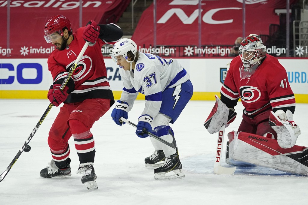 Carolina Hurricanes center Vincent Trocheck, left, reaches for the puck while Tampa Bay Lightning center Yanni Gourde (37) looks on in front of Hurric...